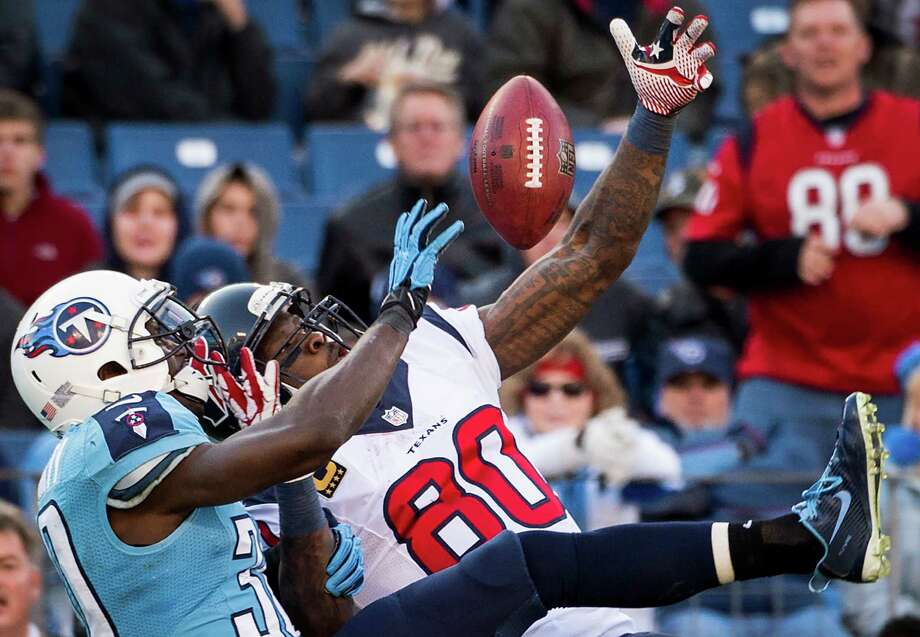 Titans cornerback Jason McCourty breaks up a second-half pass intended for Texans wide receiver Andre Johnson (80) on Sunday. With 49 yards receiving, Johnson fell 93 short of becoming the first NFL player with four seasons of 100 catches and 1,500 yards. Photo: Smiley N. Pool, Staff / © 2013  Houston Chronicle