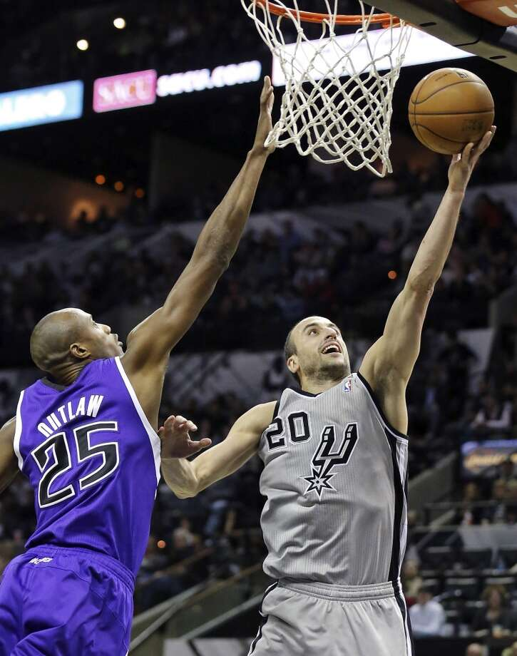 San Antonio Spurs' Manu Ginobili shoots around Sacramento Kings' Travis Outlaw during second half action Sunday Dec. 29, 2013 at the AT&T Center. The Spurs won 112-104. Photo: Edward A. Ornelas, San Antonio Express-News