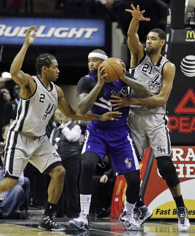 San Antonio Spurs' Kawhi Leonard and San Antonio Spurs' Tim Duncan defend Sacramento Kings' DeMarcus Cousins during second half action Sunday Dec. 29, 2013 at the AT&T Center. The Spurs won 112-104. Photo: Edward A. Ornelas, San Antonio Express-News