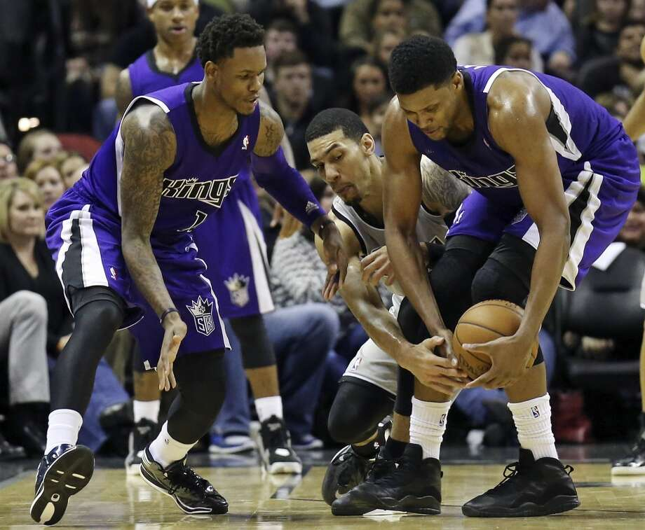San Antonio Spurs' Danny Green grabs for a loose ball between Sacramento Kings' Ben McLemore (left) and Sacramento Kings' Rudy Gay during second half action Sunday Dec. 29, 2013 at the AT&T Center. The Spurs won 112-104. Photo: Edward A. Ornelas, San Antonio Express-News