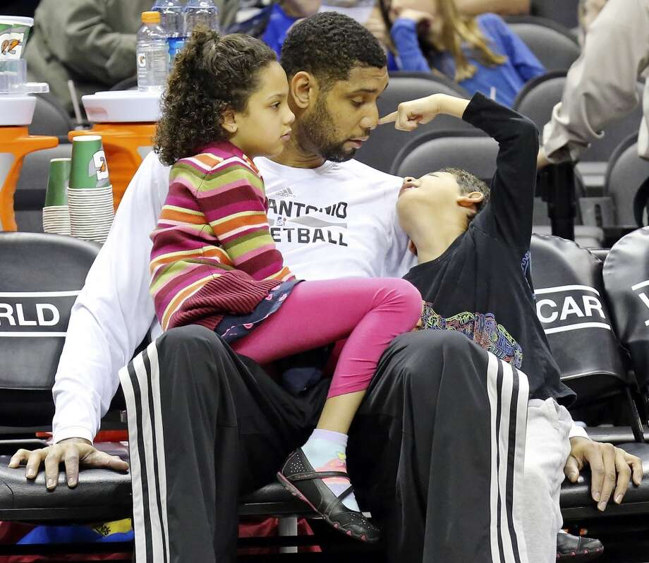 San Antonio Spurs' Tim Duncan sits with his children Sydney (left) and Draven before the game with the Sacramento Kings Sunday Dec. 29, 2013 at the AT&T Center. Photo: Edward A. Ornelas, San Antonio Express-News
