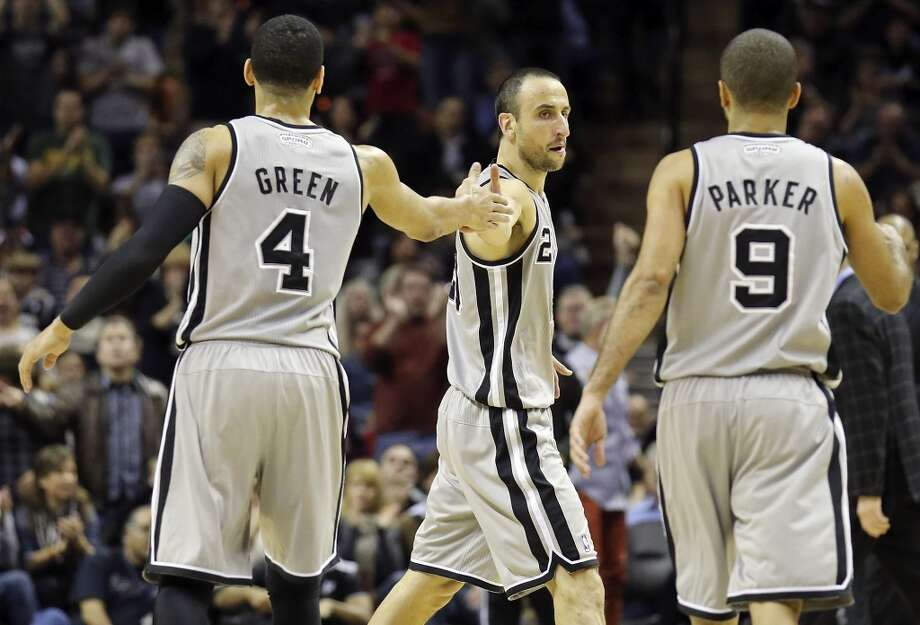 San Antonio Spurs' Manu Ginobili celebrates with teammates San Antonio Spurs' Danny Green and San Antonio Spurs' Tony Parker after making a 3-pointer during second half action against the Sacramento Kings Sunday Dec. 29, 2013 at the AT&T Center. The Spurs won 112-104. Photo: Edward A. Ornelas, San Antonio Express-News