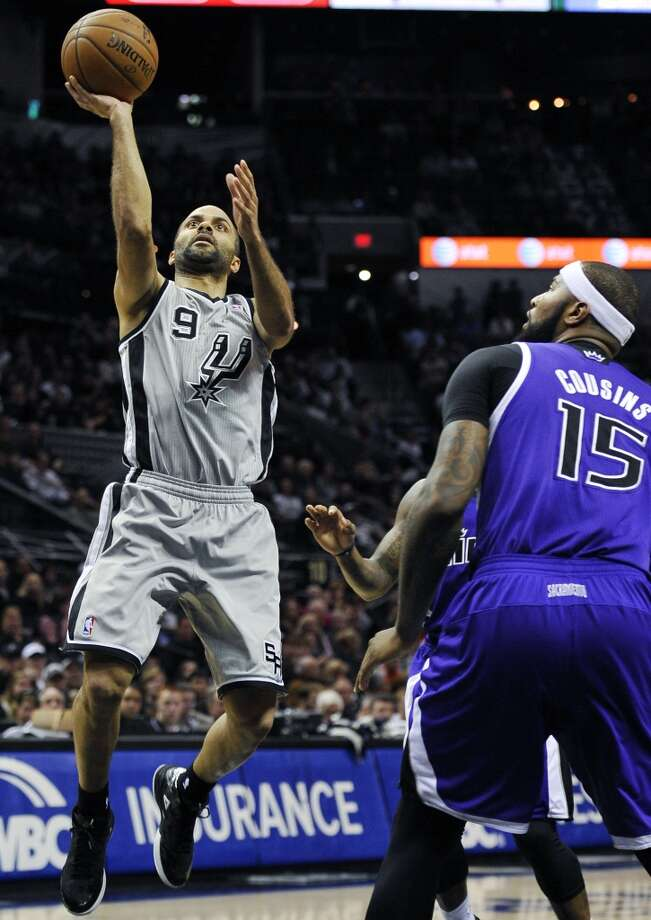 San Antonio Spurs guard Tony Parker, left, of France, shoots over Sacramento Kings center DeMarcus Cousins during the first half of an NBA basketball game on Sunday, Dec. 29, 2013, in San Antonio. Photo: Darren Abate, Associated Press