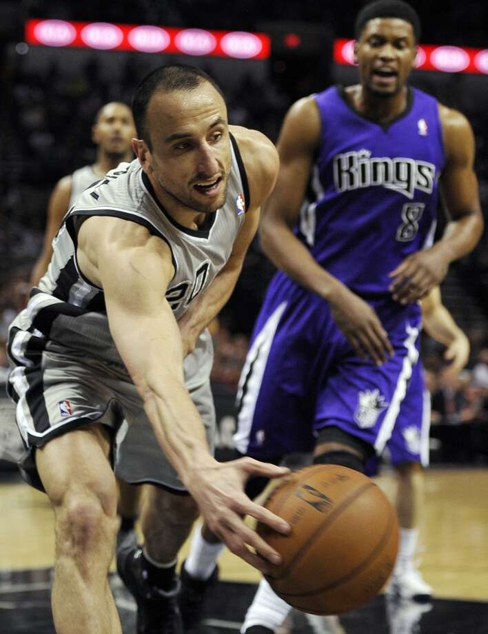 San Antonio Spurs guard Manu Ginobili, left, of Argentina, chases the loose ball ahead of Sacramento Kings forward Rudy Gay during the first half of an NBA basketball game on Sunday, Dec. 29, 2013, in San Antonio. Photo: Darren Abate, Associated Press
