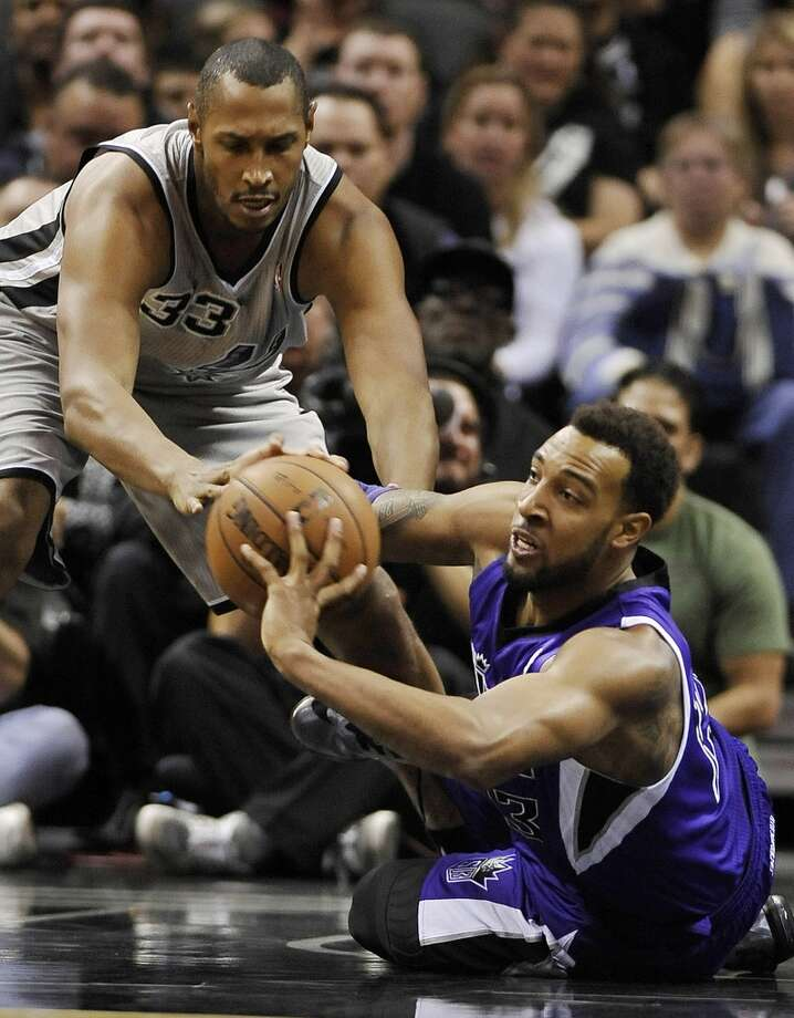 Sacramento Kings forward Derrick Williams, right, fights for the loose ball against San Antonio Spurs forward Boris Diaw, of France, during the first half of an NBA basketball game on Sunday, Dec. 29, 2013, in San Antonio. Photo: Darren Abate, Associated Press