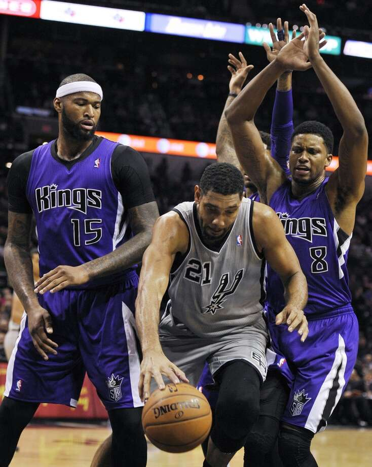 San Antonio Spurs forward Tim Duncan, center, chases tjhe loose ball against Sacramento Kings forward Rudy Gay, right, and Kings center DeMarcus Cousins, during the first half of an NBA basketball game on Sunday, Dec. 29, 2013, in San Antonio. Photo: Darren Abate, Associated Press