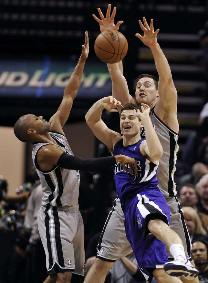 Sacramento Kings guard Jimmer Fredette, center, collides with San Antonio Spurs forward Aron Baynes, right, and Spurs guard Patty Mills, both of Australia, during the first half of an NBA basketball game on Sunday, Dec. 29, 2013, in San Antonio. Photo: Darren Abate, Associated Press