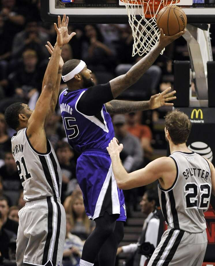 Sacramento Kings center DeMarcus Cousins, center, shoots against San Antonio Spurs forwards Tiago Splitter, right, of Brazil, and Tim Duncan, during the first half of an NBA basketball game on Sunday, Dec. 29, 2013, in San Antonio. Photo: Darren Abate, Associated Press