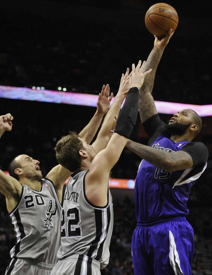 Sacramento Kings center DeMarcus Cousins, right, shoots over San Antonio Spurs forward Tiago Splitter, center, of Brazil, and Spurs guard Manu Ginobili, of Argentina, during the second half of an NBA basketball game on Sunday, Dec. 29, 2013, in San Antonio. San Antonio won 112-104. Photo: Darren Abate, Associated Press