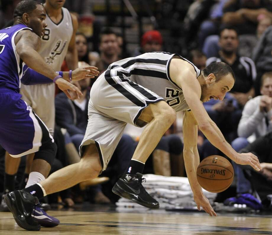 San Antonio Spurs guard Manu Ginobili, of Argentina, recovers after colliding with Sacramento Kings guard Marcus Thornton, left, during the second half of an NBA basketball game on Sunday, Dec. 29, 2013, in San Antonio. San Antonio won 112-104. Photo: Darren Abate, Associated Press