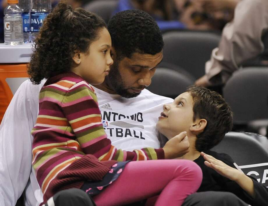 San Antonio Spurs forward Tim Duncan, center, sits with his daughter, Sydney, left, and son, Draven, before an NBA basketball game against the Sacramento Kings on Sunday, Dec. 29, 2013, in San Antonio. Photo: Darren Abate, Associated Press