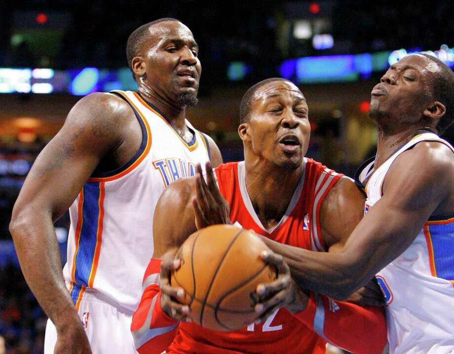 Dwight Howard tries to split the defense of  Kendrick Perkins, left, and Reggie Jackson. Photo: Alonzo Adams, FRE / FR159426 AP