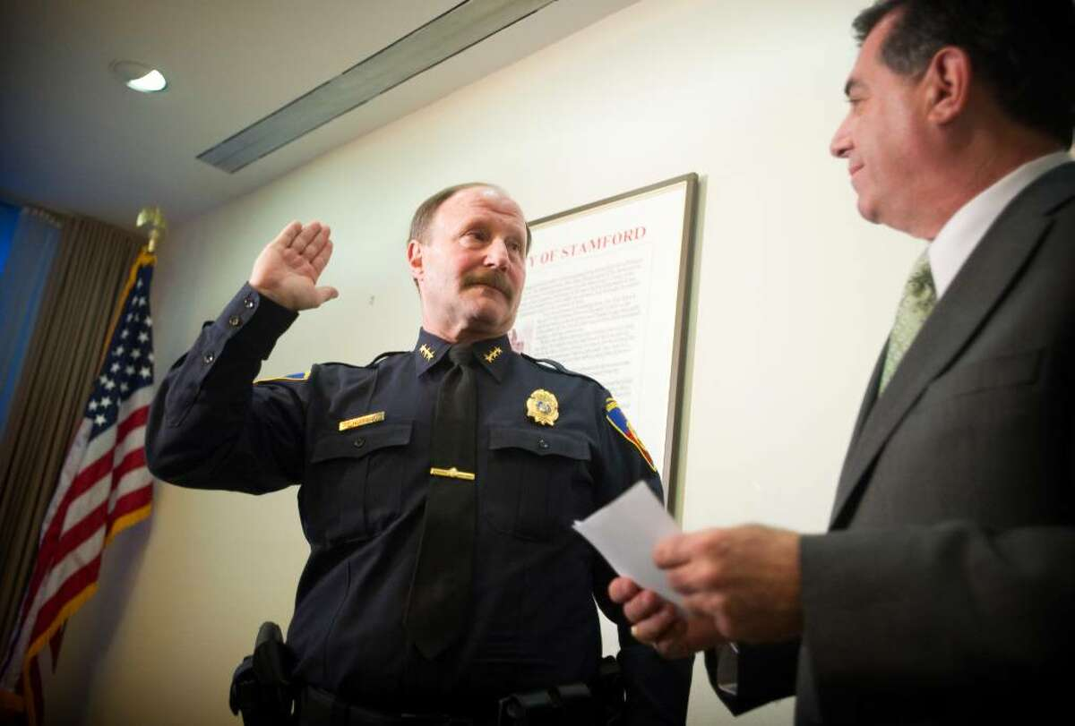 Robert Nivakoff, left, is sworn in as chief of the Stamford Police Department by Mayor Michael Pavia, right, in the Government Center on Tuesday, Feb. 2, 2010.