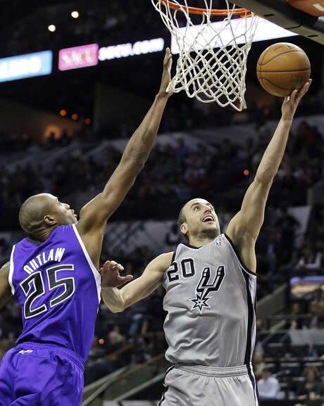 Spurs guard Manu Ginobili shoots around Sacramento forward Travis Outlaw en route to a season-best 28 points at the AT&T Center. Photo: Edward A. Ornelas, San Antonio Express-News / © 2013 San Antonio Express-News