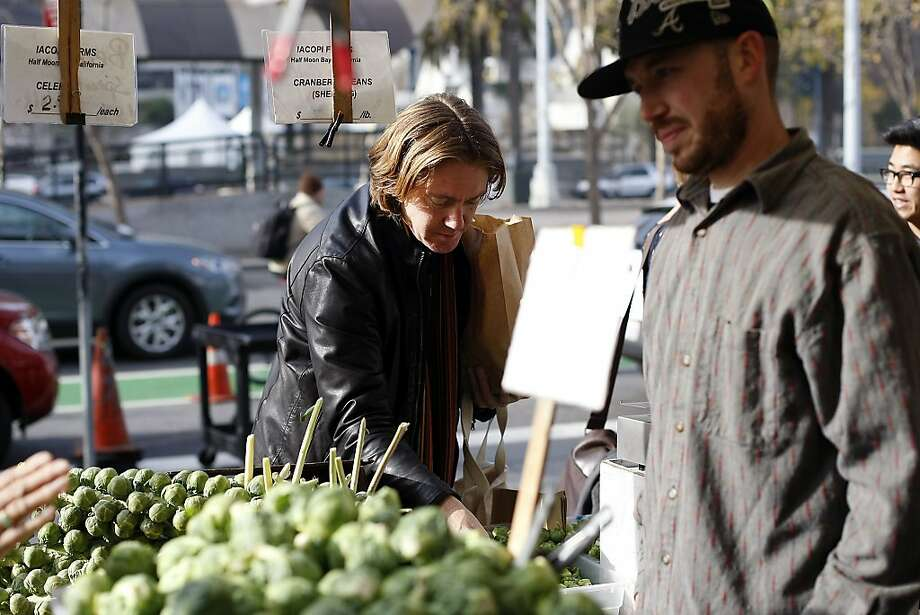 Top: Andy Katz (center) of S.F., at the Ferry Plaza Farmers Market in S.F., shops for Brussels sprouts from Iacopi Farms of Half Moon Bay and other produce, above. Photo: Michael Short, The Chronicle