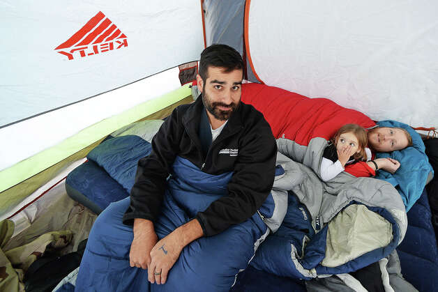 Marcus Paterno, left, and friend Jared Gilthorpe and his daughter, right, camp outside of Best Buy the day before Thanksgiving. The friends arrived to Best Buy at noon in hopes of being the first in line.  