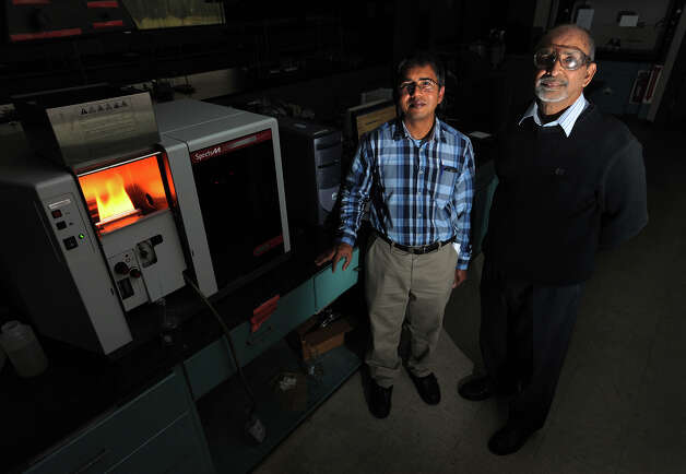 Using orange and banana peels, Andrew Gomes, left, and Shyam Shukla developed of a process to remove metals from drinking water. The two Lamar professors stand next to an atomic absorption spectrometer which burns different metals at different colors to determine types of toxicity. The machine produces a red flame, pictured, by burning calcium chloride.