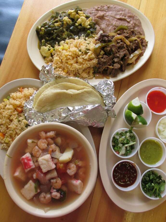 A plate with fajita beef, seafood soup (sopa de marisco) and homemade corn tortillas, along with a selection from the fresh salsa bar at El Paraiso on College Street. Photo: Cat5