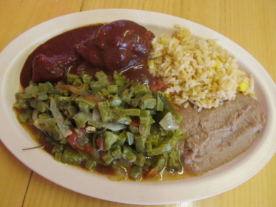 El Paraiso's steam table plate (un plato) of chicken mole, nopalitos, rice and beans. Photo: Cat5