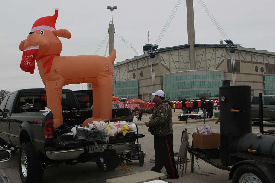 Longhorn fan Dustin Martinez sets up an inflatable reindeer in the bed of a pickup truck Monday December 30, 2013 in the parking lot of the Alamobowl before the Valero Alamo Bowl. The matchup will feature the University of Texas Longhorns against the University of Oregon Ducks. Photo: JOHN DAVENPORT, SAN ANTONIO EXPRESS-NEWS / ©San Antonio Express-News/Photo may be sold to the public