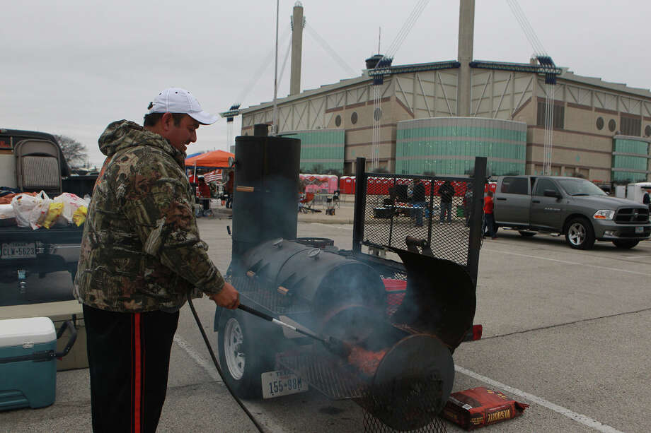 Longhorn fan Dustin Martinez lights his barbecue rig Monday December 30, 2013 in the parking lot of the Alamobowl before the Valero Alamo Bowl. The matchup will feature the University of Texas Longhorns against the University of Oregon Ducks. Photo: JOHN DAVENPORT, SAN ANTONIO EXPRESS-NEWS / ©San Antonio Express-News/Photo may be sold to the public