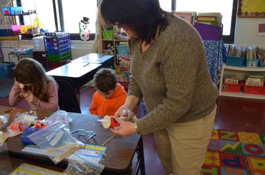 Deanne Macrina volunteered to help make holiday crafts with Heather Casullo's second grade class. Photo: Ashley Bellinger