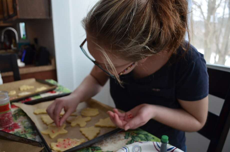 Kayla Heath, age 17, decorates Christmas themed cookies. Photo: Ashley Bellinger