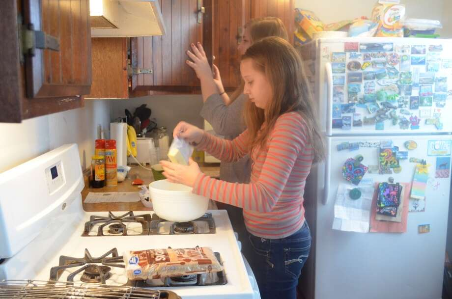 Sisters, Megan and Riley  Longendyke making cookies together for friends and family. Photo: Audrey Goodemote