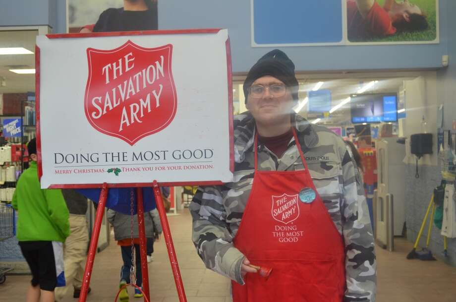 Salvation army volunteer ringing a bell with a smile in Glenmont. Photo: Audrey Goodemote
