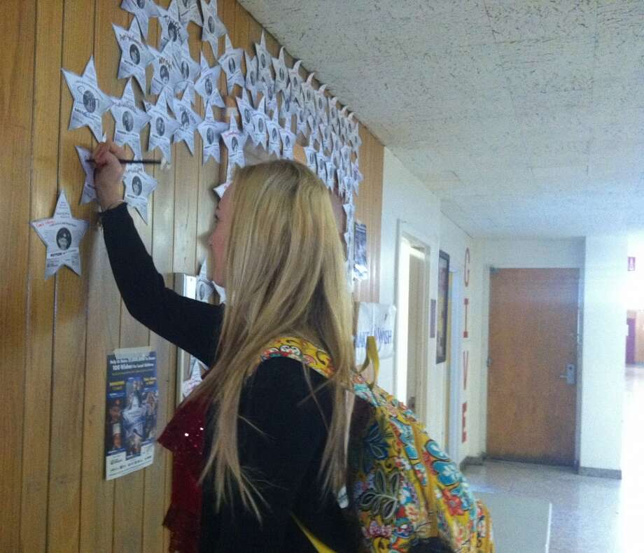 Senior Avé Williams signs a star in support of the Make-A-Wish foundation hosted at Scotia-Glenville High School. Photo: Olivia Dunn