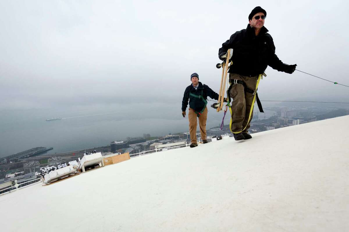 Brian Morningstar, right, and Scott Streeper, center, from Pyro Spectaculars, work to install several thousand pyrotechnic shots used to create the upcoming ?'T-Mobile New Year?•s at the Needle?