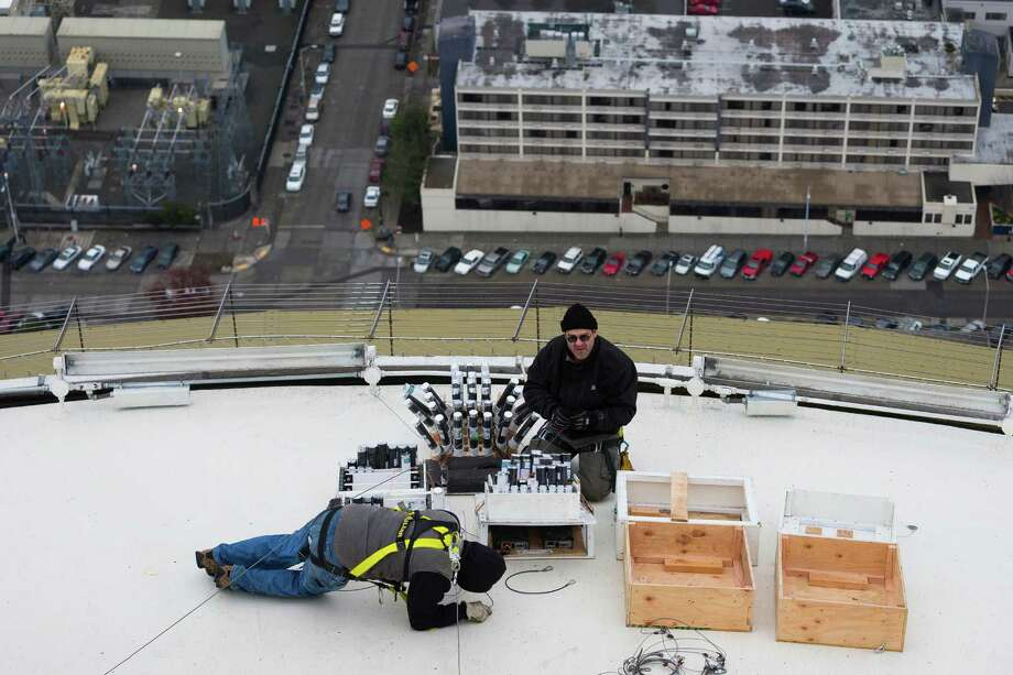 Brian Morningstar, center, and crews from Pyro Spectaculars work to install several thousand pyrotechnic shots used to create the upcoming ÒT-Mobile New YearÕs at the NeedleÓ fireworks display Monday, Dec. 30, 2013, at the top of the Space Needle in Seattle. The show lasts eight minutes in total and will be set to a musical score of contemporary pop, rock and hip hop. Photo: JORDAN STEAD, SEATTLEPI.COM / SEATTLEPI.COM