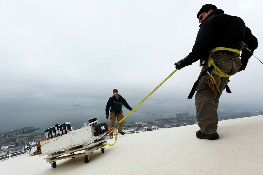 Brian Morningstar, right, and Scott Streeper, center, from Pyro Spectaculars, work to install several thousand pyrotechnic shots used to create the upcoming ÒT-Mobile New YearÕs at the NeedleÓ fireworks display Monday, Dec. 30, 2013, at the top of the Space Needle in Seattle. The show lasts eight minutes in total and will be set to a musical score of contemporary pop, rock and hip hop. Photo: JORDAN STEAD, SEATTLEPI.COM / SEATTLEPI.COM