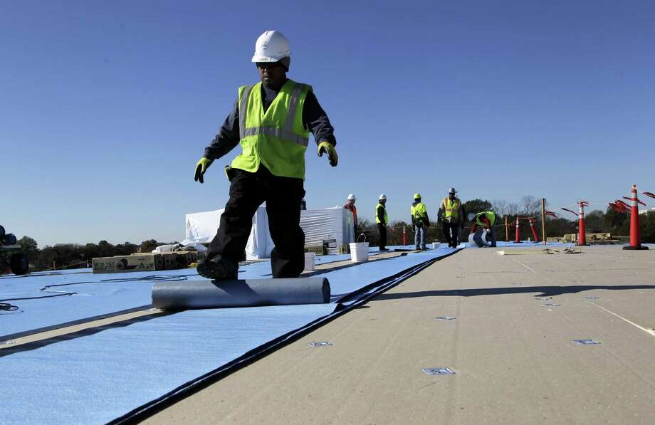 Workers For Baker Roofing Co. Put Down An Ice And Water Shield As They  Install