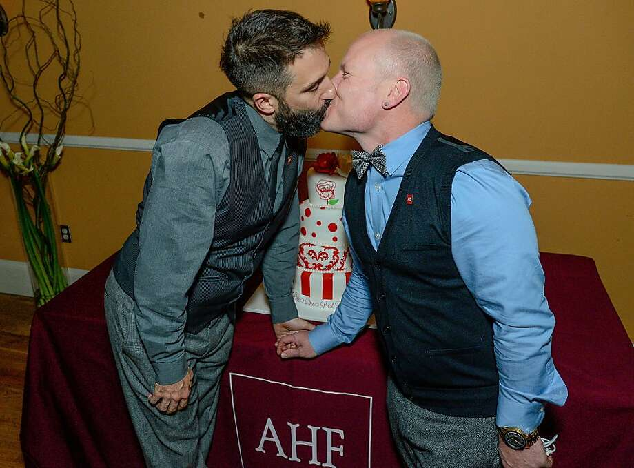 Danny Leclair (left) and Aubrey Loots kiss in front of their cake. They're marrying on a Rose Parade float. Photo: Eric Reed, Associated Press