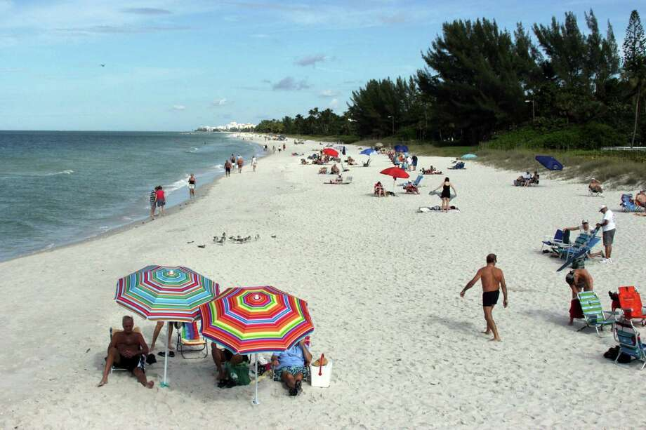 Vacationers to Naples, Fla., find a spot on the beach in the relative calm of December. Crowds tend to increase in January. Photo: Ellen Creager, MBR / Detroit Free Press