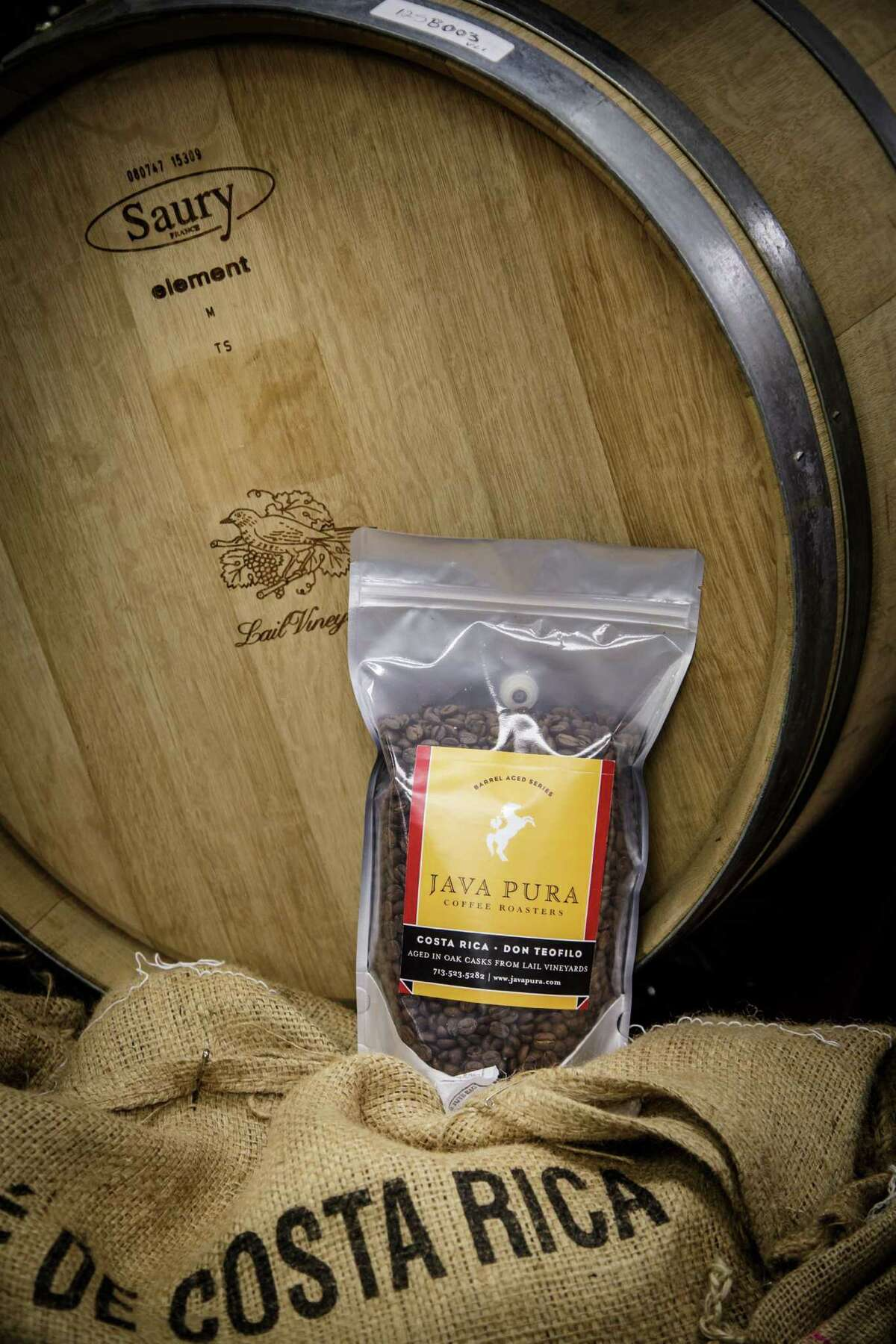 Coffee beans aged within a wine cask sit packaged at Java Pura, Monday, Oct. 7, 2013, in Houston. Java Pura has been experimenting with aging coffee beans in wine and beer casks causing the beans to pick up the nuances of wine and food before they are roasted. The oak barrels originate from Lail Vineyards of Napa Valley (both Sauvignon Blanc and Cabernet Sauvignon) and Saint Arnold brewery in Houston. ( Michael Paulsen / Houston Chronicle )