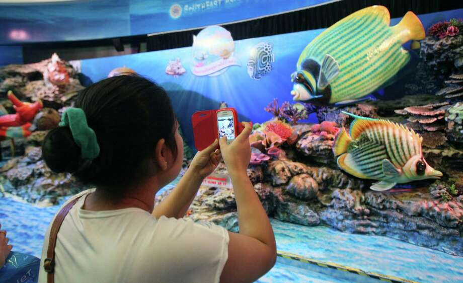 In this photo taken on Monday, Dec. 16, 2013, a visitor uses her mobile phone to take a picture of an aquatic animal display at Siam Ocean World,  located in Siam Paragon shopping mall in Bangkok Monday,  Dec. 16, 2013. Siam Paragon has claimed this year's crown as the world's most photographed location on Instagram. It edged out No. 2 Times Square and No. 3 Disneyland in California on the list that also includes New York's Central Park and Dodger Stadium in Los Angeles. (AP Photo/Sakchai Lalit) Photo: Sakchai Lalit, STF / AP