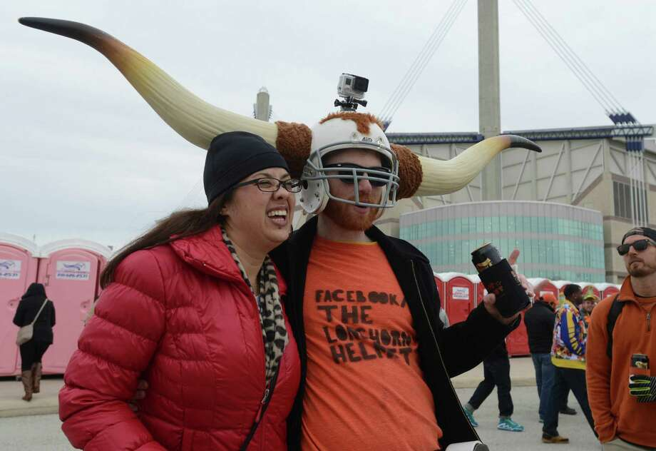 "Bryan Makin wears what he calls ""The Longhorn Helmet"" as he poses for a picture with Vicki S. Porter before the Valero Alamo Bowl at the Alamdome on Monday, Dec. 30, 2013. Photo: Billy Calzada, San Antonio Express-News / San Antonio Express-News"