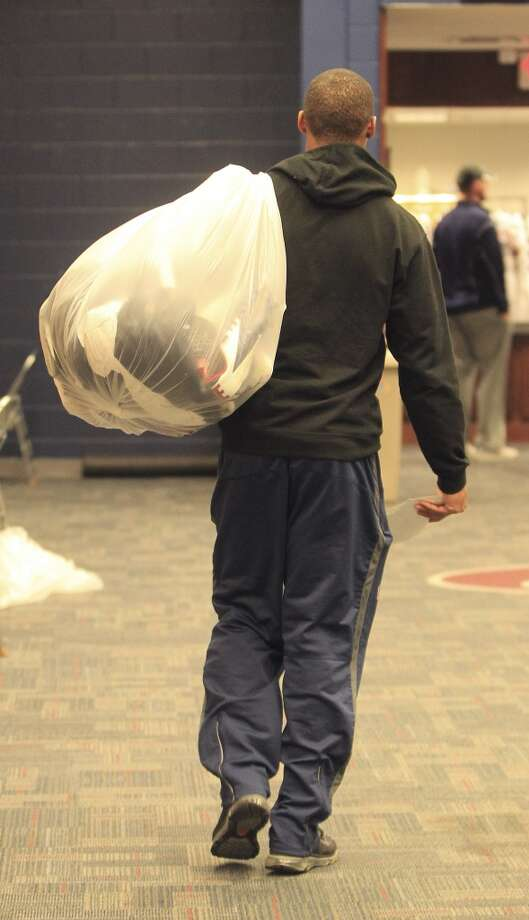 Texans quarterback T.J. Yates leaves with a bag of his belongings. Photo: Karen Warren, Houston Chronicle