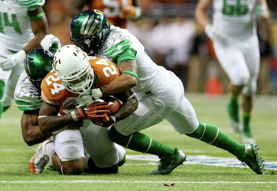 Running back Joe Bergeron #24 of the Texas Longhorns is tackled by linebacker Boseko Lokombo #25 and defensive back Brian Jackson #12 of the Oregon Ducks during the Valero Alamo Bowl at the Alamodome on December 30, 2013 in San Antonio, Texas. Photo: Ronald Martinez, Getty Images / 2013 Getty Images