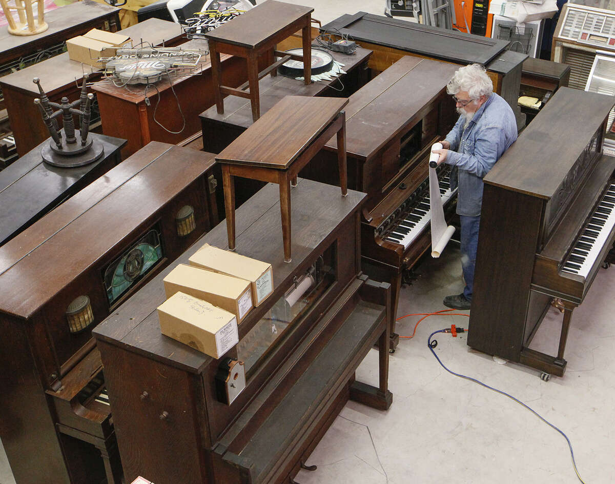 Ragtime Southwest owner John Talbot replaces a music roll in one of the many player pianos in his shop on FM 78 outside Converse. He's been in the player piano restoration-conversion business since 1996, and says he's fortunate to be able to work at something he likes to do.