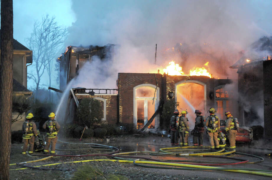 Montgomery County firefighters battle the blaze at the home in the 11490 block of Grand Pine on Monday. Photo: Jerry Baker, For The Chronicle