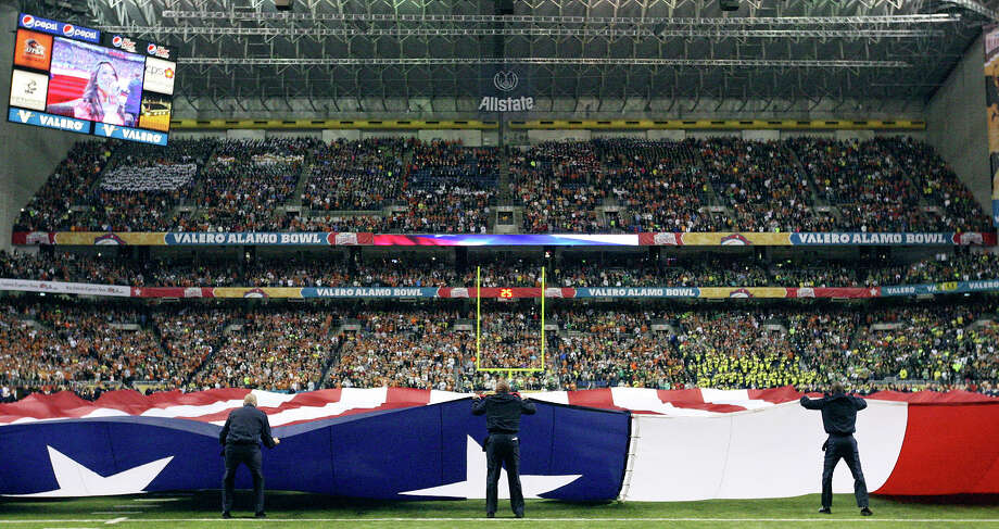 A giant American flag fills the field before the Valero Alamo Bowl Monday Dec. 30, 2013 at the Alamodome. Photo: Edward A. Ornelas, San Antonio Express-News / © 2013 San Antonio Express-News