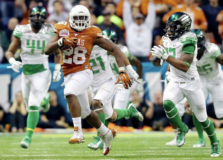 Texas Longhorns' Malcolm Brown looks for running room around Oregon Ducks defenders during first half action of the Valero Alamo Bowl Monday Dec. 30, 2013 at the Alamodome. Photo: Edward A. Ornelas, San Antonio Express-News / © 2013 San Antonio Express-News