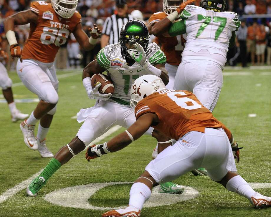 Wide receiver Bralon Addison of Oregon (11) tries to avoid Texas tackler Quandre Diggs (6) during first-half action of the Valero Alamo Bowl in the Alamdome on Monday, Dec. 30, 2013. Photo: Billy Calzada, San Antonio Express-News / San Antonio Express-News