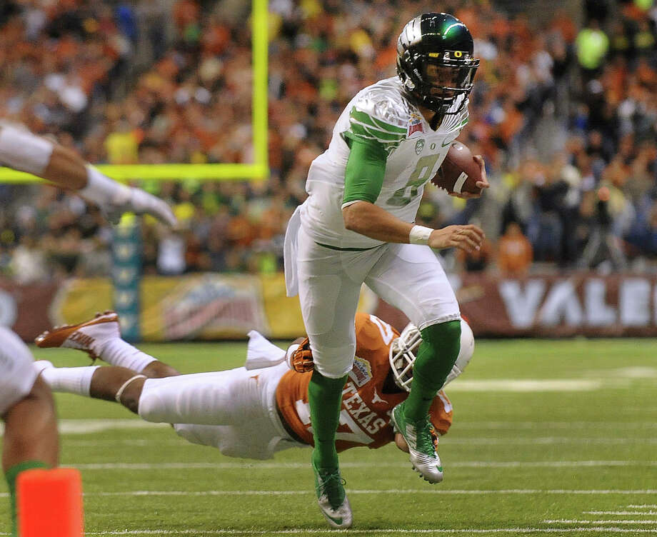 Oregon quarterback Marcus Mariota (8) runs toward the goal line as defender Adrian Philips of Texas gives chase during first-half action of the Valero Alamo Bowl in the Alamdome on Monday, Dec. 30, 2013. Photo: Billy Calzada, San Antonio Express-News / San Antonio Express-News