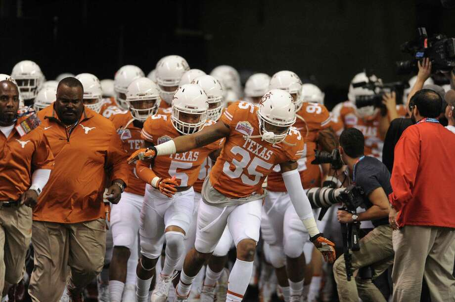 The Texas Longhorns enter the field for their Valero Alamo Bowl matchup against Oregon in the Alamdome on Monday, Dec. 30, 2013. Photo: Billy Calzada, San Antonio Express-News / San Antonio Express-News
