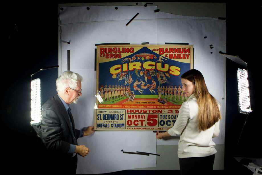 Laney Dwyer, assistant manager and lead archivist at the Julia Ideson Library and Joel Draut, communications specialist, place a circus poster from the Heiser-Alban Collection of Circus Historical Materials to be photographed for the archive at the Julia Ideson Library Thursday, Dec. 12, 2013, in Houston. 