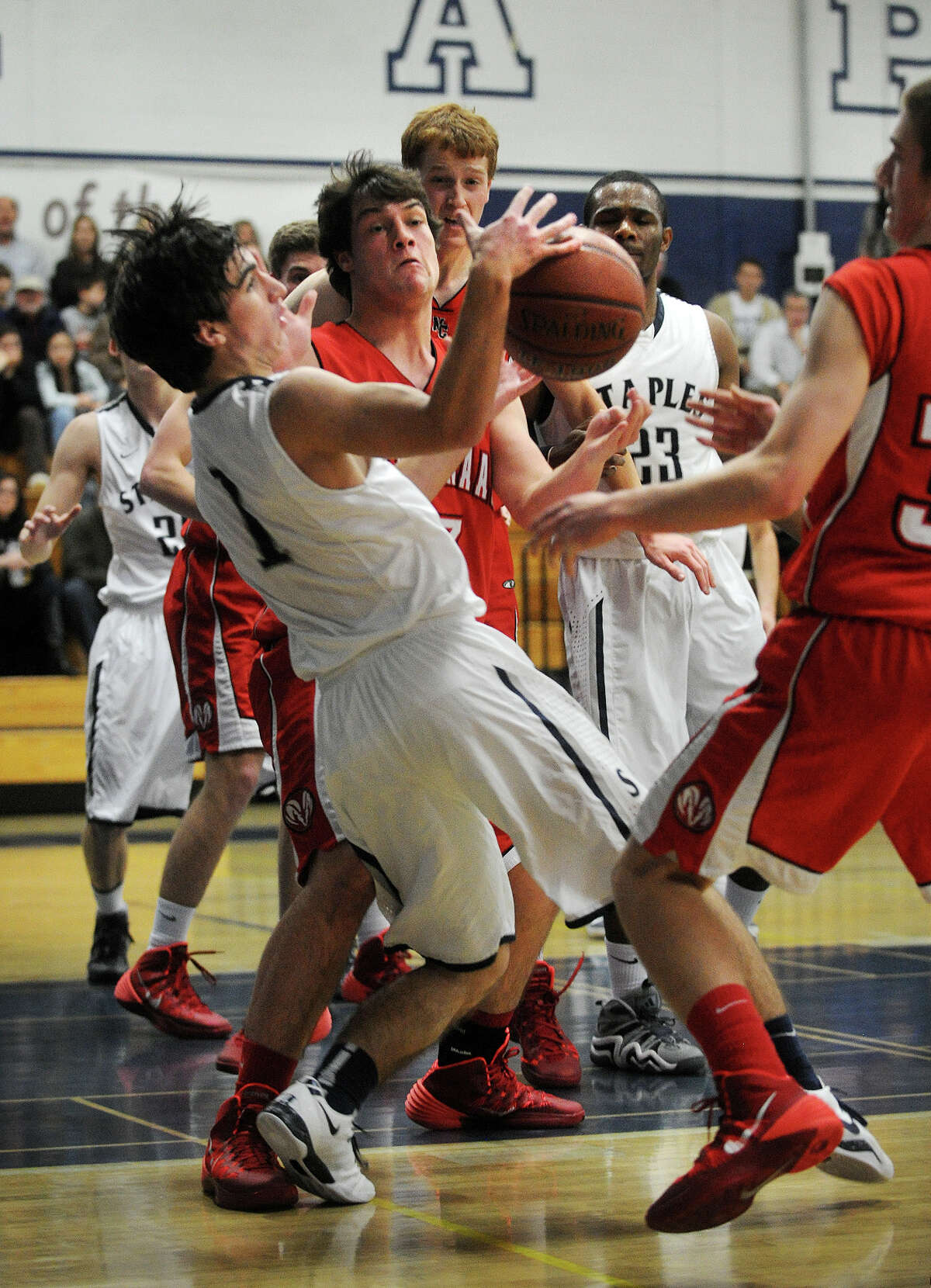 Staples' Jake Melnick, left, battles for a loose ball during the Wreckers' boys basketball win over New Canaan at Staples High School in Westport, Conn. on Monday, December 30, 2013.
